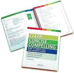 Two copies of the first edition of Clear Concise Compelling, with one opened to reveal the spiral binding